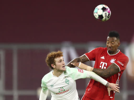 Bremen's Joshua Sargent, left, jumps for the ball with Bayern's Jerome Boateng during the German Bundesliga soccer match between FC Bayern Munich and SV Werder Bremen in Munich, Germany, Saturday, Nov. 21, 2020. (AP Photo/Matthias Schrader)