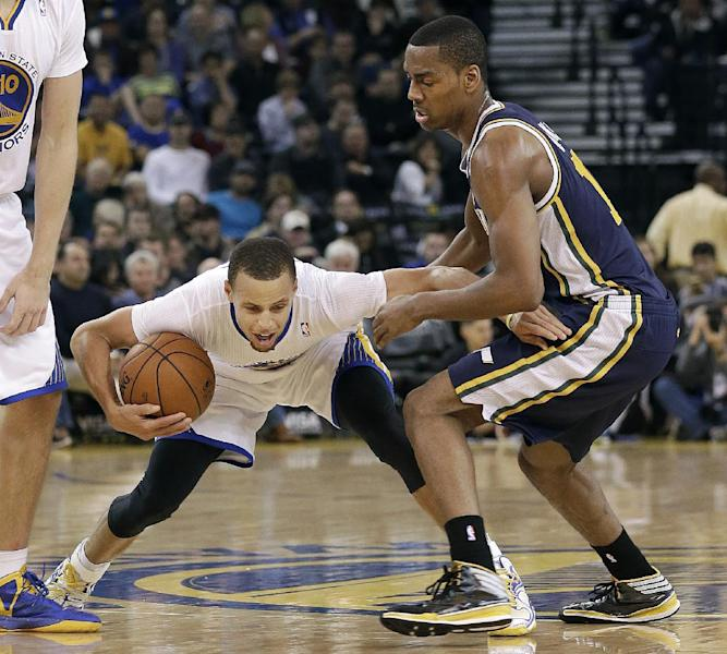Golden State Warriors shooting guard Stephen Curry, left, tries to dribble past Utah Jazz point guard Alec Burks during the second quarter of an NBA basketball game in Oakland, Calif., Saturday, Nov. 16, 2013. (AP Photo/Jeff Chiu)