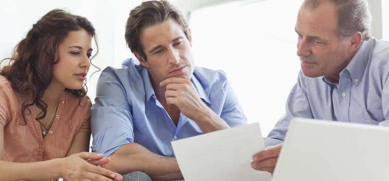 Young couple sits with adult male looking at paperwork.
