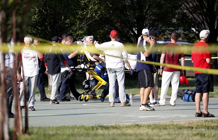 <p>A person is loaded on a stretcher as members of the Republican congressional baseball team look on following a shooting in Alexandria, Va, June 14, 2017. (Photo: Shawn Thew/EPA) </p>