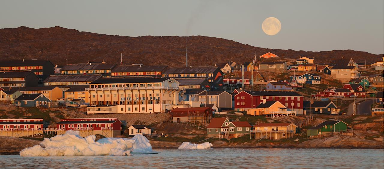 ILULISSAT, GREENLAND - JULY 24: The village of Ilulissat is seen near the icebergs that broke off from the Jakobshavn Glacier on July 24, 2013 in Ilulissat, Greenland. As the sea levels around the globe rise, researchers affilitated with the National Science Foundation and other organizations are studying the phenomena of the melting glaciers and its long-term ramifications. The warmer temperatures that have had an effect on the glaciers in Greenland also have altered the ways in which the local populace farm, fish, hunt and even travel across land. In recent years, sea level rise in places such as Miami Beach has led to increased street flooding and prompted leaders such as New York City Mayor Michael Bloomberg to propose a $19.5 billion plan to boost the citys capacity to withstand future extreme weather events by, among other things, devising mechanisms to withstand flooding. (Photo by Joe Raedle/Getty Images)
