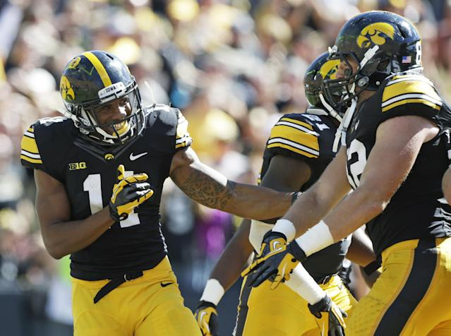 Iowa's Kevonte Martin-Manley, left, celebrates with teammate Ray Hamilton after returning a punt 63-yards for a touchdown during the first half of an NCAA college football game, Saturday, Sept. 21, 2013, in Iowa City, Iowa. (AP Photo/Charlie Neibergall)