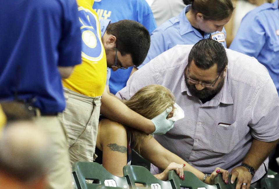 A fan is helped after being hit by a foul ball.