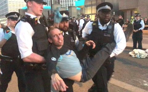 Screengrab from a video of Olympic gold medalist Etienne Stott being arrested by police at the Extinction Rebellion demonstration on Waterloo Bridge in London - Credit: PA