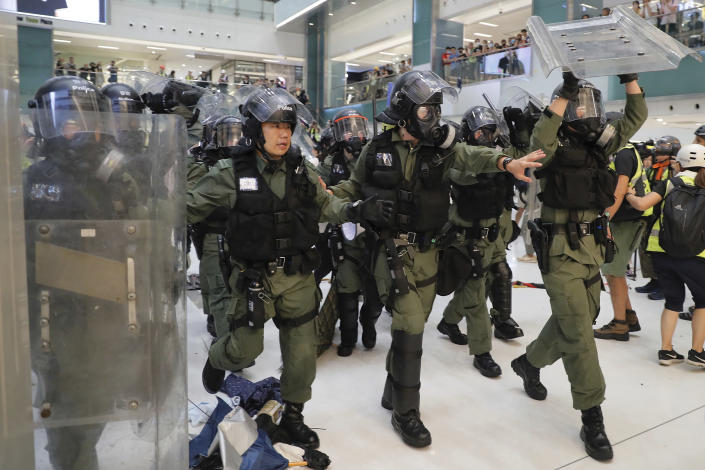 Riot policemen move in to clear the protesters inside a mall in Sha Tin District in Hong Kong, Sunday, July 14, 2019. Police in Hong Kong have fought with protesters as they broke up a demonstration by thousands of people demanding the resignation of the Chinese territory's chief executive and an investigation into complains of police violence. (AP Photo/Kin Cheung)
