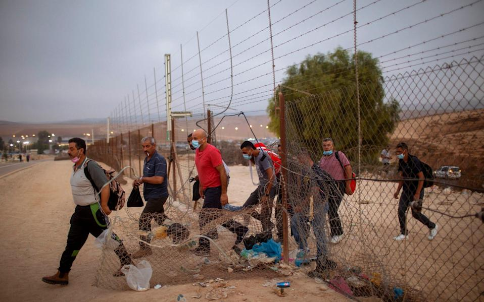 Palestinian labourers cross into Israel through a hole in a fence south of Hebron - AP