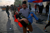 An injured protester is rushed to a hospital during clashes with security forces on the closed Joumhouriya Bridge that leads to the Green Zone government areas, in Baghdad, Iraq, Sunday, Oct. 25, 2020. Thousands of Iraqi protesters have taken to the streets to mark one year since mass anti-government demonstrations swept Baghdad and Iraq's south. Protesters marched Sunday in the capital and several southern cities to renew demands to bring an end to corruption perpetuated by Iraq's politicians. (AP Photo/Khalid Mohammed)