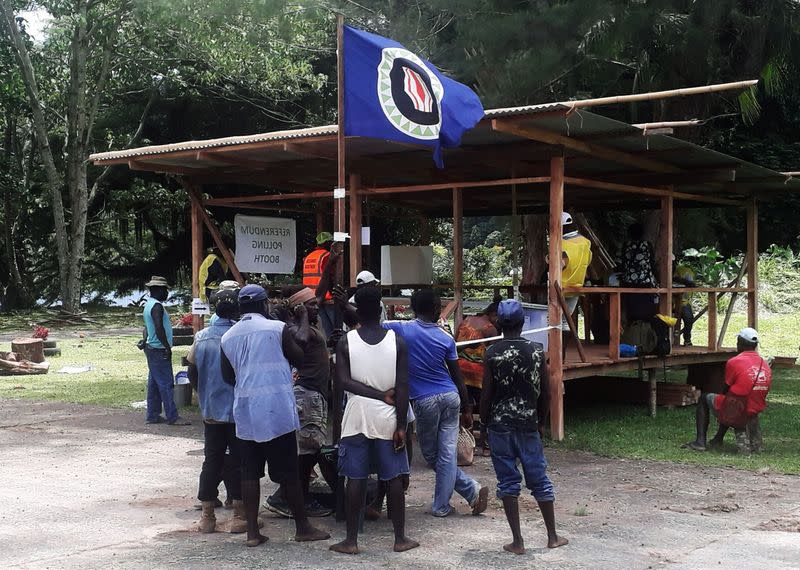Residents hold a Bougainville flag at a polling station during a non-binding independence referendum in Arawa