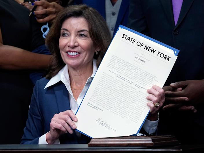 """New York Gov. Kathy Hochul holds the """"Less is More"""" law she signed, during ceremonies in the her office, in New York, Friday, Sept. 17, 2021."""