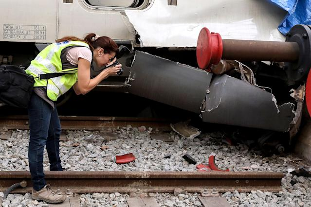 <p>A railway technician photographs damage at a train wagon at the Estacio de Franca (Franca station) in central Barcelona on July 28, 2017 after a regional train appears to have hit the end of the track inside the station injuring dozens of people. (Photo: Miquel Llop/NurPhoto via Getty Images) </p>