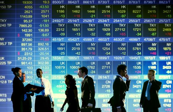 People superimposed on display of stock prices.