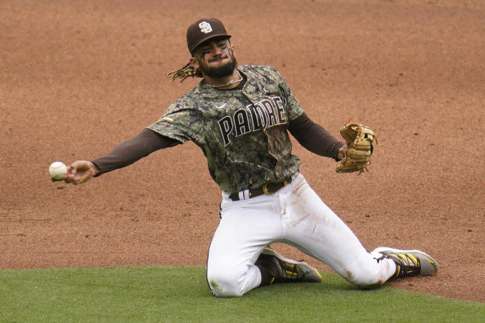 San Diego Padres shortstop Fernando Tatis Jr., throws to first from his knees in time for the out on San Francisco Giants' Wilmer Flores during the fifth inning of a baseball game Sunday, May 2, 2021, in San Diego. San Francisco Giants Tommy La Stella scored from third on the play. (AP Photo/Gregory Bull)