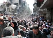 """FILE -- In this Jan. 31, 2014, file photo, released by the United Nations Relief and Works Agency for Palestine Refugees in the Near East (UNRWA), shows residents of the besieged Palestinian camp of Yarmouk, queuing to receive food supplies, in Damascus, Syria. In one besieged neighborhood after another, weary rebels have turned over their weapons to the Syrian government in exchange for an easing of suffocating blockades that have prevented food, medicine and other staples from reaching civilians trapped inside. The government touts the truces as part of its program of """"national reconciliation"""" to end Syria's crisis, which has killed more than 140,000 people since March 2011. (AP Photo/UNRWA, File)"""