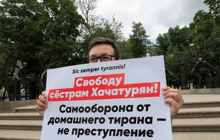A man holds a placard during a rally in support of three Khachaturyan sisters, who accused of killing their father, in Moscow