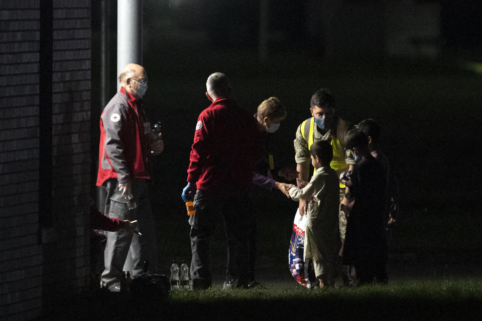 Passengers evacuated from Afghanistan are greeted by health personel upon disembarking from a British Royal Air Force (RAF) Airbus KC2 Voyager aircraft, after landing at RAF Brize Norton station in southern England on August 24, 2021. - Britain said on August 23 it would urge the United States to extend an end-of-the-month deadline for evacuations from Afghanistan, while the Taliban warned any delay would lead to