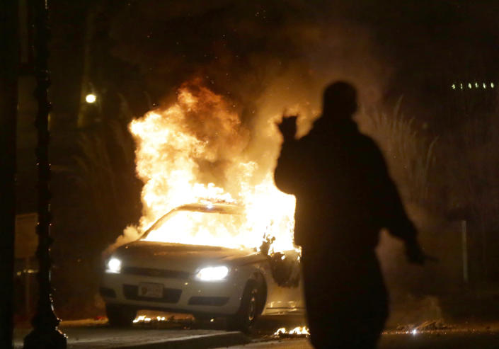 FILE - In this Nov. 24, 2014, file photo, a police car is set on fire amid protests that followed the announcement that a grand jury had declined to indict Ferguson police officer Darren Wilson in the death of Michael Brown. (AP Photo/Charlie Riedel, File)
