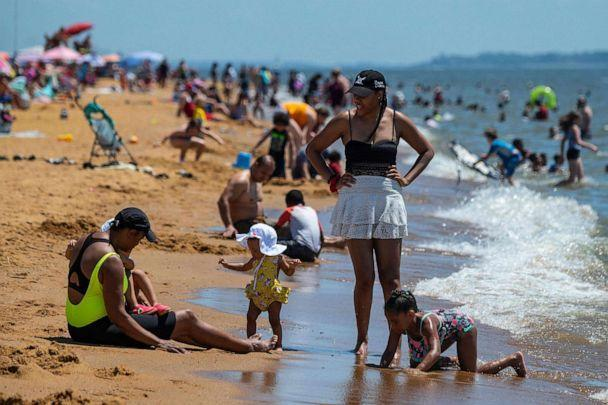 PHOTO: People play on the beach as they try to escape the heat at Sandy Point State Park in Annapolis, Md., June 29, 2021. (Jim Watson/AFP via Getty Images)