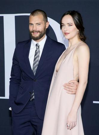 "FILE PHOTO - Cast members Jamie Dornan (L) and Dakota Johnson pose at the premiere of the film ""Fifty Shades Darker"" in Los Angeles, California, U.S. on February 2, 2017. REUTERS/Danny Moloshok/File Photo"