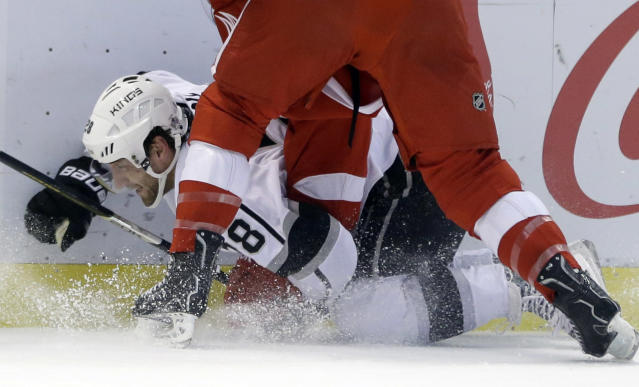 Los Angeles Kings center Jarret Stoll (28) is checked by Detroit Red Wings right wing Luke Glendening during the first period of an NHL hockey game in Detroit, Saturday, Jan. 18, 2014. (AP Photo/Carlos Osorio)
