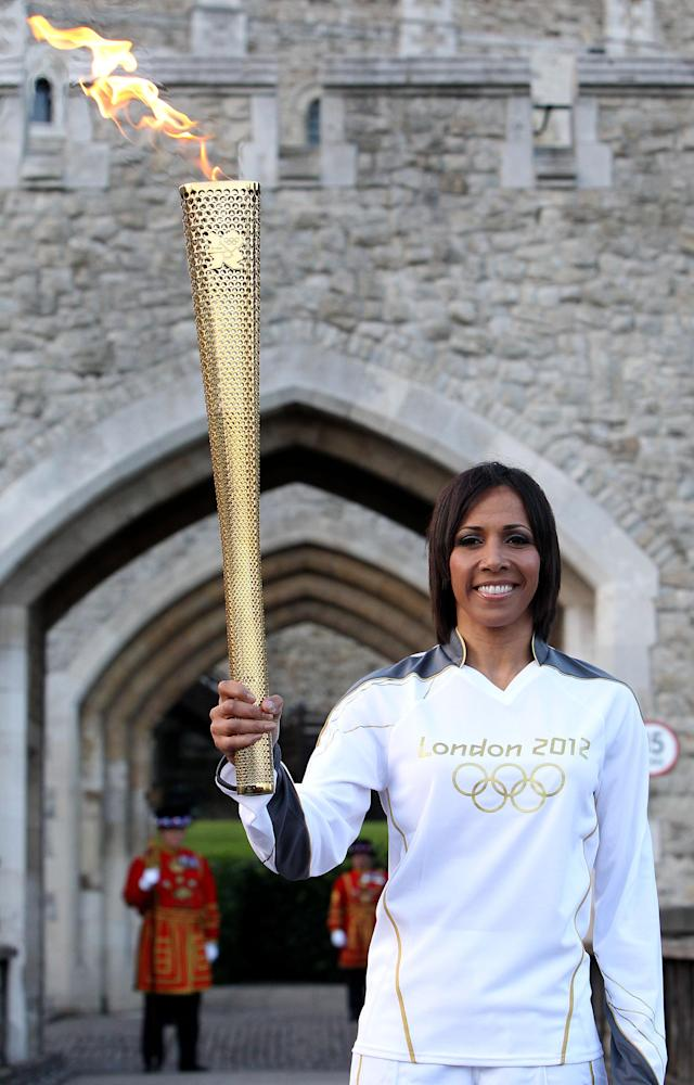 LONDON, ENGLAND - JULY 20: Dame Kelly Holmes poses with the torch at the Tower of London during the London 2012 Olympic Torch Relay on July 20, 2012 in London, England. The Olympic Flame is now on day 63 of a 70-day relay involving 8,000 torchbearers covering 8,000 miles. (Photo by Jan Kruger/Getty Images)