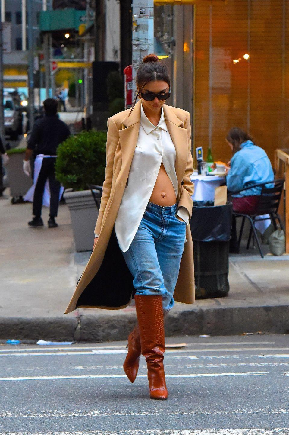 <p>The model was spotted out in New York City in October, wearing a white shirt styled open to reveal her growing bump. She teamed it with jeans, a camel coat and some knee-high boots.</p>