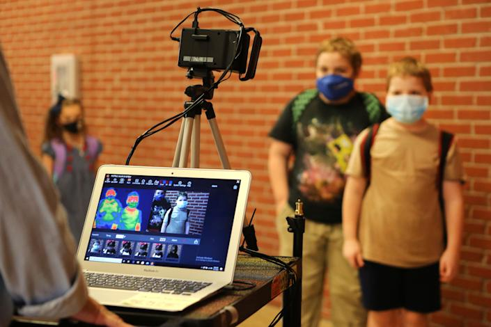 Corinth Elementary School students have their temperature checked by a thermal scanner as they arrive for their first day back to school July 27 in Corinth, Miss.