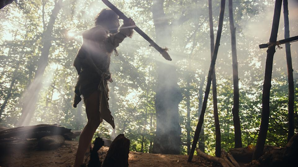 Primeval Caveman Wearing Animal Skin Holds Stone Tipped Spear, Stands at the Cave Entrance Looking over Prehistoric Forest Ready to Hunt Animal Preys. Neanderthal Going Hunting in the Jungle