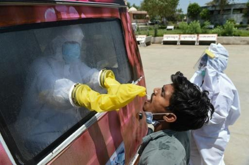 A health official uses a swab to collect a sample from a man for COVID-19 testing at a mobile testing van near Ahmedabad, India