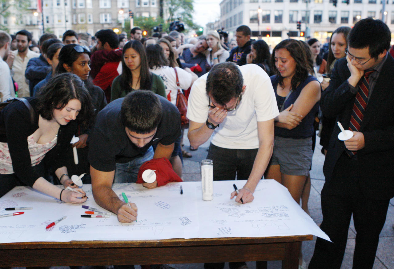 Boston University students gather to sign a condolence note prior to a candlelight vigil on Marsh Plaza at Boston University, Saturday, May 12, 2012, in Boston, for three students studying in New Zealand who were killed when their minivan crashed during a weekend trip. At least five other students were injured in the accident, including one who was in critical condition. Boston University spokesman Colin Riley said those killed in the accident were Daniela Lekhno, 20, of Manalapan, N.J.; Austin Brashears, 21, of Huntington Beach, Calif.; and Roch Jauberty, 21, whose parents live in Paris. (AP Photo/Bizuayehu Tesfaye)