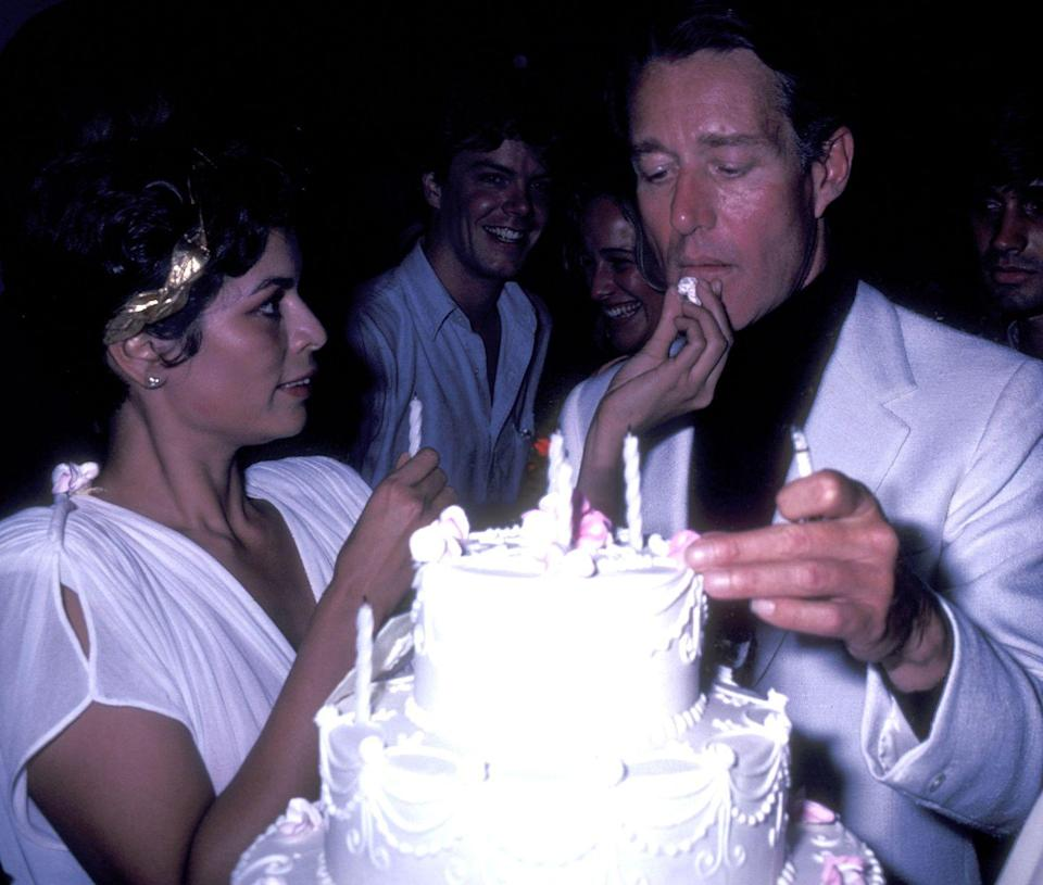 <p>Bianca Jagger celebrates her 35th birthday at the New York nightclub, Bond's. Here, the model feeds cake to her dear friend, Halston, as she celebrates the milestone. One person notably absent is her ex-husband, Mick Jagger, who she divorced in 1978. </p>