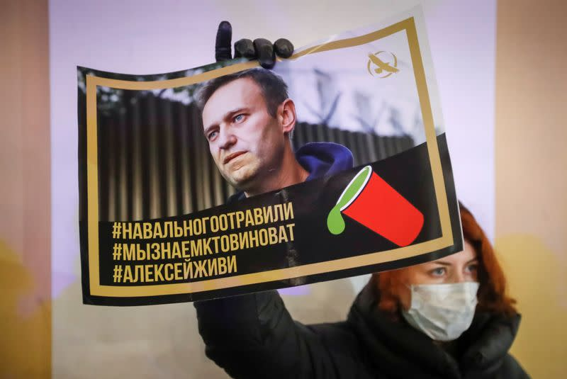 FILE PHOTO: An activist holds a portrait of opposition politician Alexei Navalny during a picket in his support in Saint Petersburg