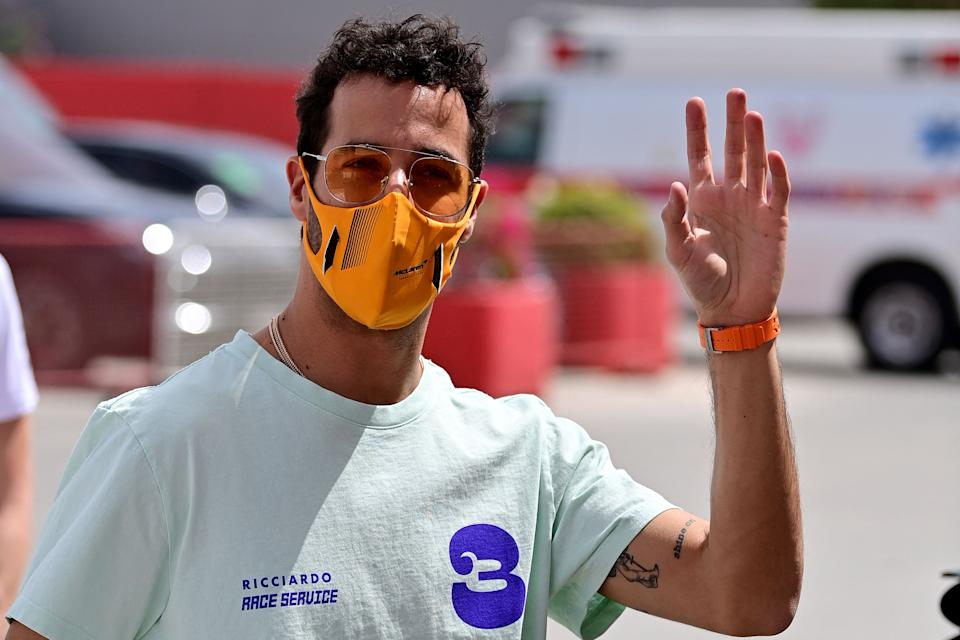 McLaren driver Daniel Ricciardo waves as he arrives at the paddock on March 25, 2021.