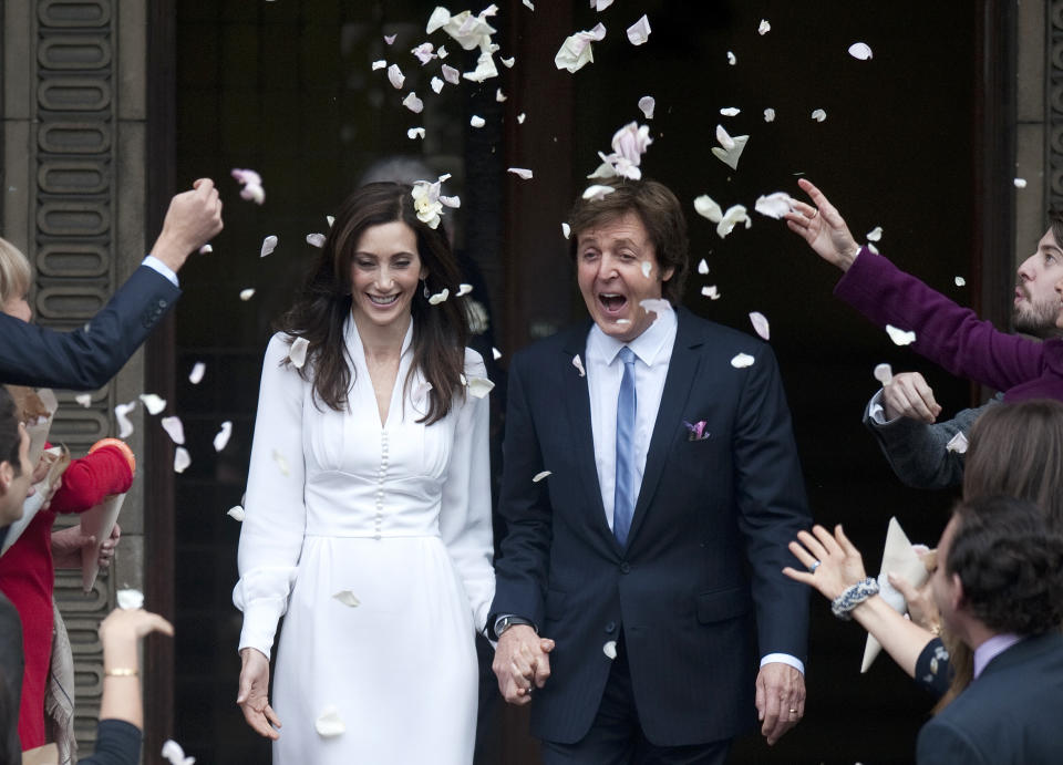 Singer Paul McCartney and his bride Nancy Shevell are showered in confetti as they leave after their marriage ceremony at Old Marylebone Town Hall in London October 9, 2011.  Former Beatle Paul McCartney wed for the third time on Sunday when he and New York heiress Nancy Shevell were married in a civil ceremony in London.   REUTERS/Kieran Doherty  (BRITAIN - Tags: ENTERTAINMENT)