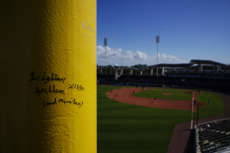 Baseball fans sign a pole near the Green Monster seating area during a spring training baseball game with the Atlanta Braves and the Boston Red Sox on Monday, March 1, 2021, in Fort Myers, Fla. (AP Photo/Brynn Anderson)