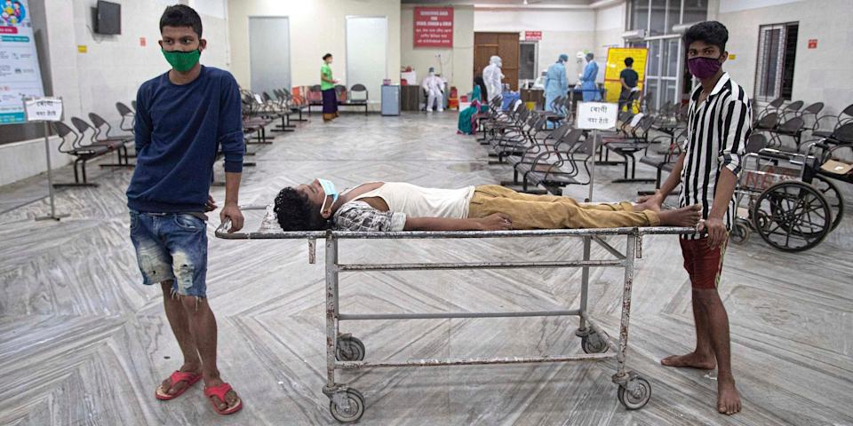 Hospital attendants with a man with a fever lying on a stretcher awaiting a coronavirus swab test at Guwahati Medical College Hospital in Assam, India, on May 17, 2020.