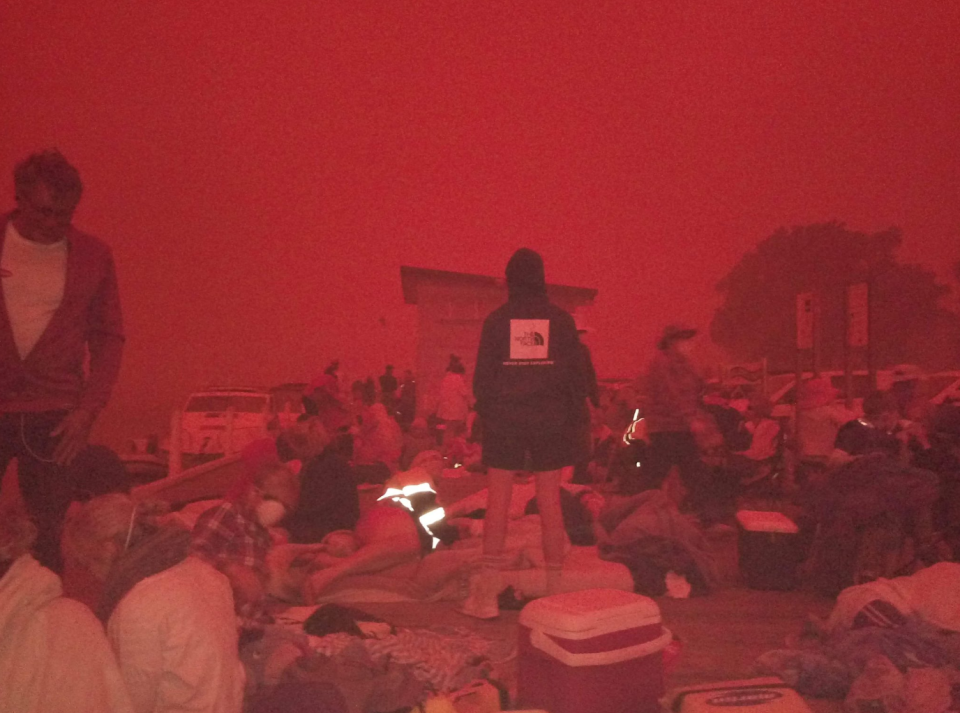 Pictured is Mallacoota residents on the shoreline on Tuesday amid the Victoria bushfires.
