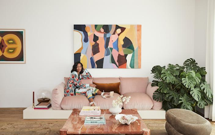 "Actor Laura Harrier lounges in Oscar de la Renta pajamas atop her vintage sofa. To adjust it to Laura's height (she's five feet nine) and add a ""side table,"" interior designer Tiffany Howell built a floating platform underneath. Painting by Jessalyn Brooks. Fashion styling by Danielle Goldberg."