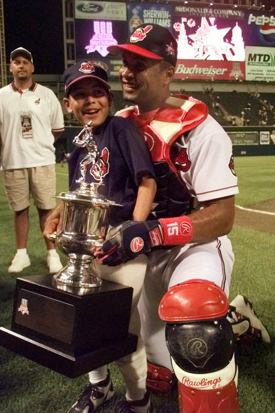 FILE - In this July 8, 1997, file photo, Cleveland Indians' Sandy Alomar shows off his MVP trophy with his son, Marcus, after the All-Star baseball game in Cleveland. With the game tied 1-1 in the seventh inning, Alomar, who had overcome serious knee issues that had threatened to derail his career, connected for a two-run homer that sent the crowd of 44,916 in perpetually sold-out Jacobs Field into delirium and pushed the AL to a 3-1 win. And while the home run was special for Alomar, his most vivid memory of that July night came after the game. (AP Photo/Beth A. Keiser, File)