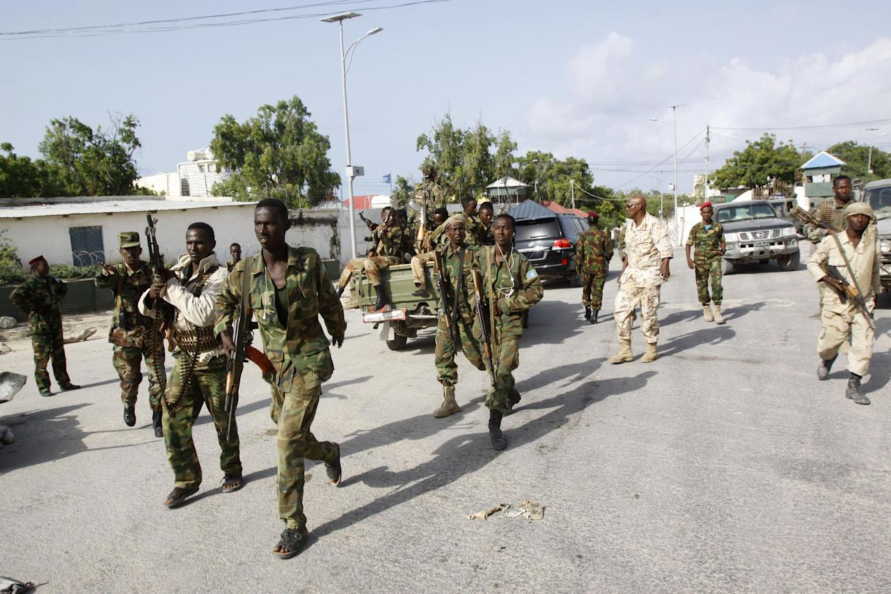 Somali soldiers patrol near the wreckage of a car bomb that was detonated at the main gate of the presidential palace in Mogadishu, Somalia, Wednesday, July, 9, 2014. Somali troops retook the presidential palace in the capital of Mogadishu after militants forced their way in and exchanged heavy gunfire with troops and guards Tuesday, the latest attack underscoring the threat posed by Islamic extremist group al-Shabab in east Africa. (AP Photo/Farah Abdi Warsameh)