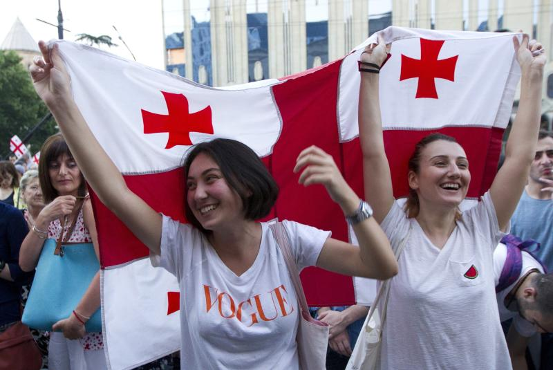 Opposition demonstrators wave Georgian national flags as they gather in front of the Georgian Parliament building in Tbilisi, Georgia, Monday, June 24, 2019. Demonstrators have returned to parliament for daily rallies, demanding the release of those detained, the ouster of the nation's interior minister and changes in the electoral law to have legislators chosen fully proportionally rather than the current mix of party-list and single-mandate representatives. (AP Photo/Shakh Aivazov)