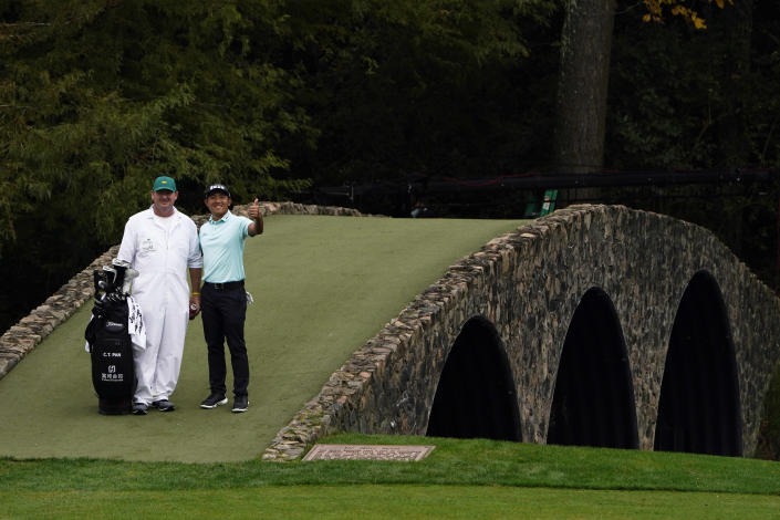 C.T. Pan, of Taipei, poses with his caddie on the Ben Hogan Bridge during a practice round for the Masters golf tournament Tuesday, Nov. 10, 2020, in Augusta, Ga. (AP Photo/Chris Carlson)