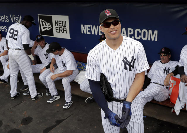 New York Yankees' Giancarlo Stanton looks out from the dugout before a baseball spring exhibition game against the Detroit Tigers, Friday, Feb. 23, 2018, in Tampa, Fla. Stanton is wearing a hat to honor the victims of the mass shooting at Marjory Stoneman Douglas High School. (AP Photo/Lynne Sladky)