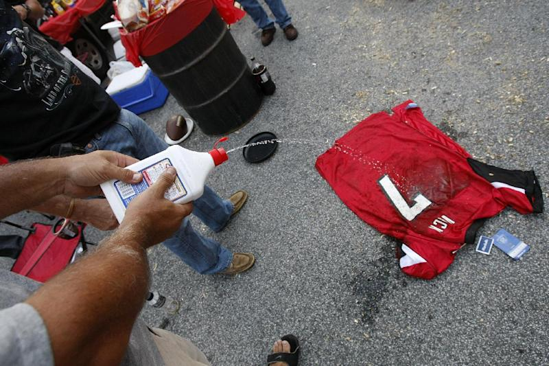 "Atlanta Falcons fan Mike Laymon, Douglasville, GA., squirts lighter fluid on a Michael Vick jersey as he prepare to set it on fire in the ""Gulch,"" a fan parking lot outside the Georgia Dome, before the Falcons play the Eagles on Sunday, Sept. 18, 2011. He started his last game in the Georgia Dome for the Falcons in 2006, a loss in which he played badly, but Michael Vick still has a powerful hold on some Falcons fans both pro and con.   (AP Photo/Atlanta Journal-Constitution, Curtis Compton)"