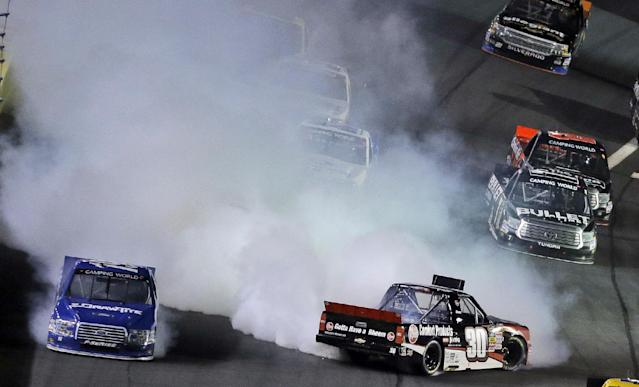 Ron Hornaday Jr. (30) spins in Turn 4 as Brad Keselowski, left, avoids a collision during the NASCAR Truck series auto race in Concord, N.C., Friday, May 16, 2014. (AP Photo/Gerry Broome)