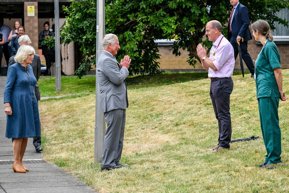 The Prince of Wales remains socially distanced as he a performs a namaste to Professor Mark Pietroni as he arrives with the Duchess of Cornwall at Gloucestershire Royal Hospital to meet front line key workers who who have responded to the COVID-19 pandemic during a visit to Gloucestershire Royal Hospital.