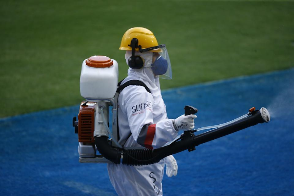 RIO DE JANEIRO, BRAZIL - OCTOBER 25: A member of the cleaning team sanitizes the stadium during the match between Fluminense and Santos as part of the Brasileirao Series A at Maracana Stadium on October 25, 2020 in Rio de Janeiro, Brazil. (Photo by Bruna Prado/Getty Images)