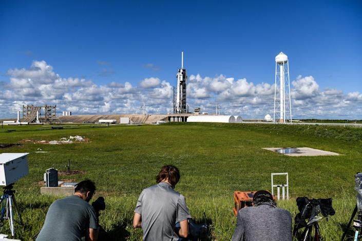 Media crew set up their equipment as the SpaceX Falcon 9 rocket and Crew Dragon is seen in the background sitting on launch Pad 39A at NASAs Kennedy Space Center, as it is prepared for the first completely private mission to fly into orbit in Cape Canaveral, Florida on September 15, 2021.