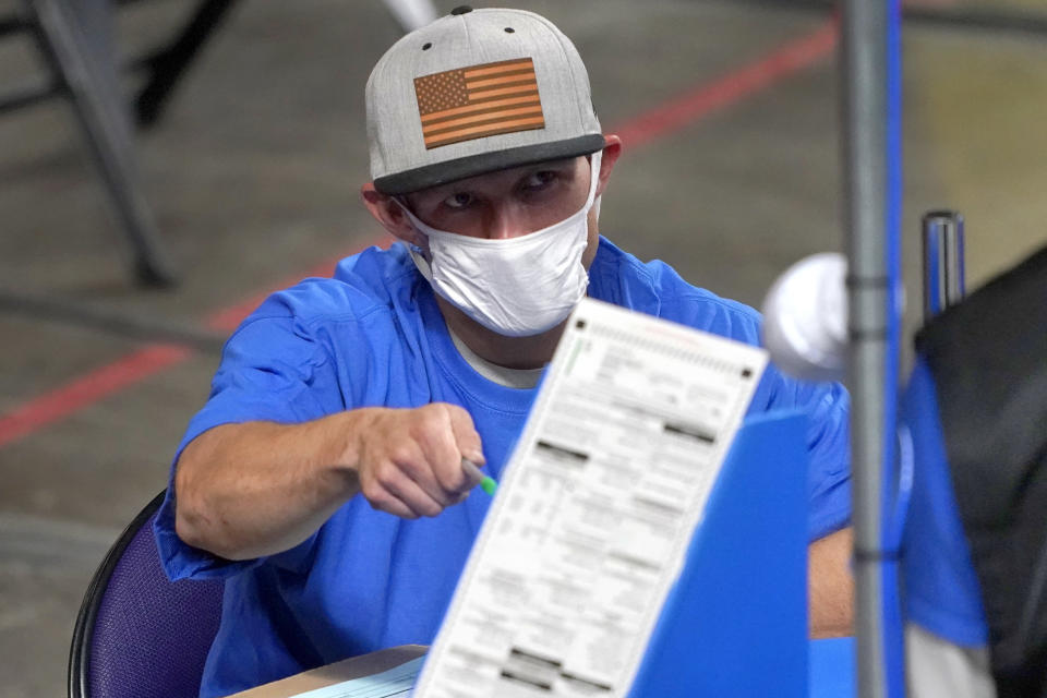 FILE - In this May 6, 2021, file photo, Maricopa County ballots cast in the 2020 general election are examined and recounted by contractors working for Florida-based company, Cyber Ninjas, at Veterans Memorial Coliseum in Phoenix. Cyber Ninjas, the inexperienced contractor hired to run a partisan review of the 2020 election on behalf of Republicans in the Arizona Senate, is scheduled to present its findings to top GOP lawmakers on Friday, Sept. 24, 2021. Election experts say the review, funded almost entirely by supporters of former President Donald Trump who have promoted false claims of fraud, was beset by problems and incompetence. (AP Photo/Matt York, Pool)