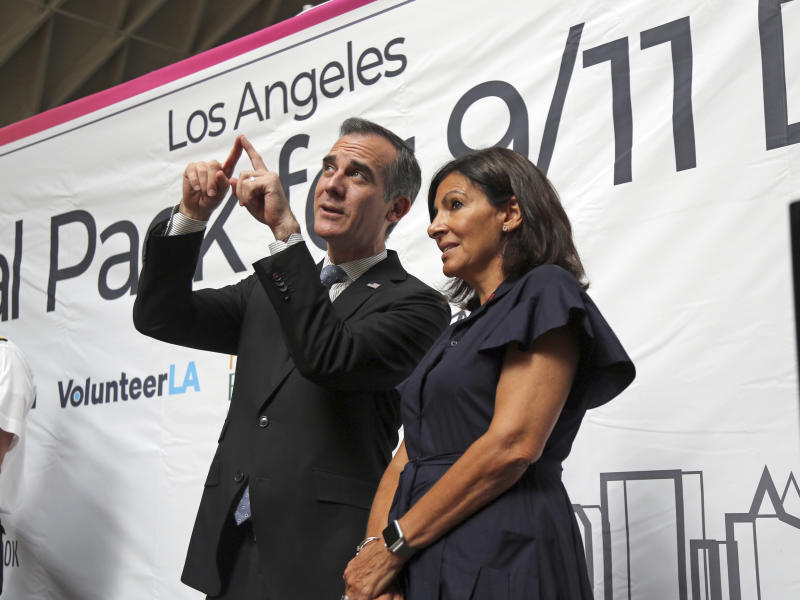 Los Angeles Mayor Eric Garcetti and Paris Mayor Anne Hidalgo share a moment following a ceremony marking the 17th anniversary of the Sept. 11, 2001 terrorist attacks on America, at the Los Angeles Fire Department's training center Tuesday, Sept. 11, 2018. Americans looked back on 9/11 Tuesday with tears and somber tributes. Victims' relatives said prayers for their country, pleaded for national unity and pressed officials not to use the 2001 terror attacks as a political tool in a polarized nation. (AP Photo/Reed Saxon)