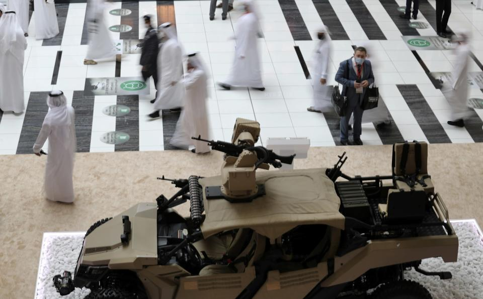 Visitors and officials pass by Sahm, a light tactical armoured vehicle assembled in UAE, during the opening day of the International Defence Exhibition & Conference, IDEX, in Abu Dhabi, United Arab Emirates, Sunday, Feb. 21, 2021. (AP Photo/Kamran Jebreili)